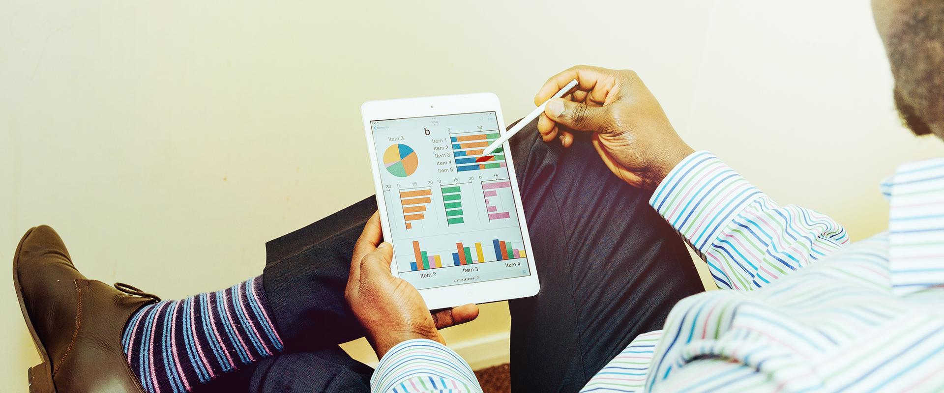 homme qui tient iPad avec graphique de stratégie marketing