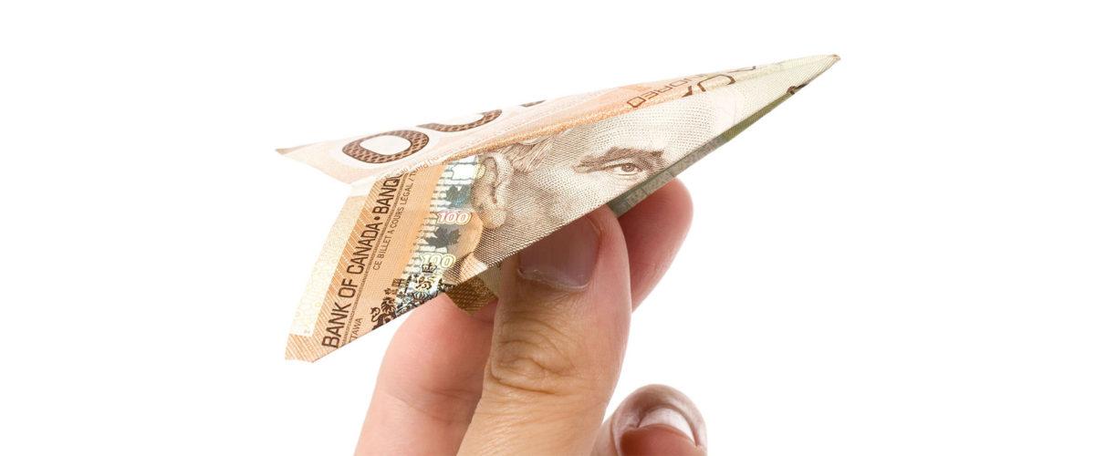 Billet plié en forme d'avion en papier tenu dans une main