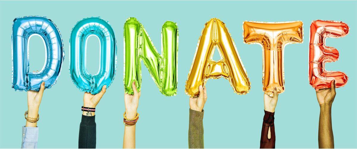 Personnes qui tiennent des ballons en forme de lettres qui forment le mot : DONATE