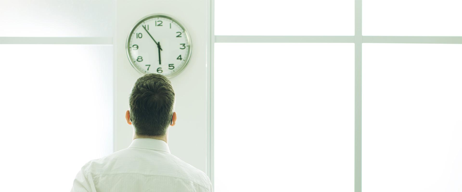 Homme attendant devant une horloge