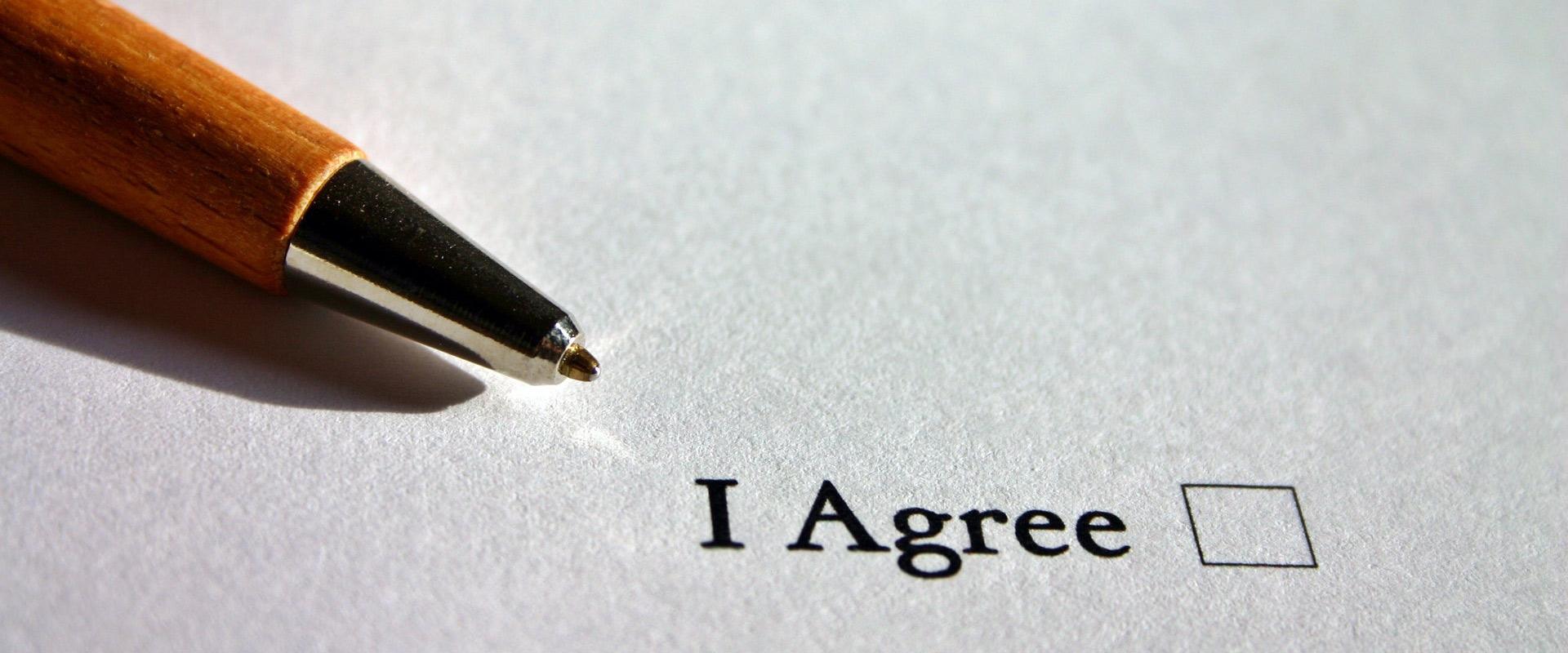 """stylo posé sur une feuille où est inscrit """"i agree"""" faisant référence au consentement"""