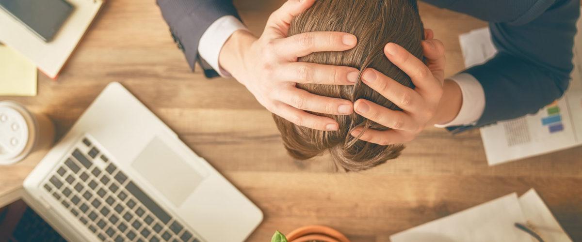 Homme en situation de travail se prenant la tête avec ses mains face à un problème