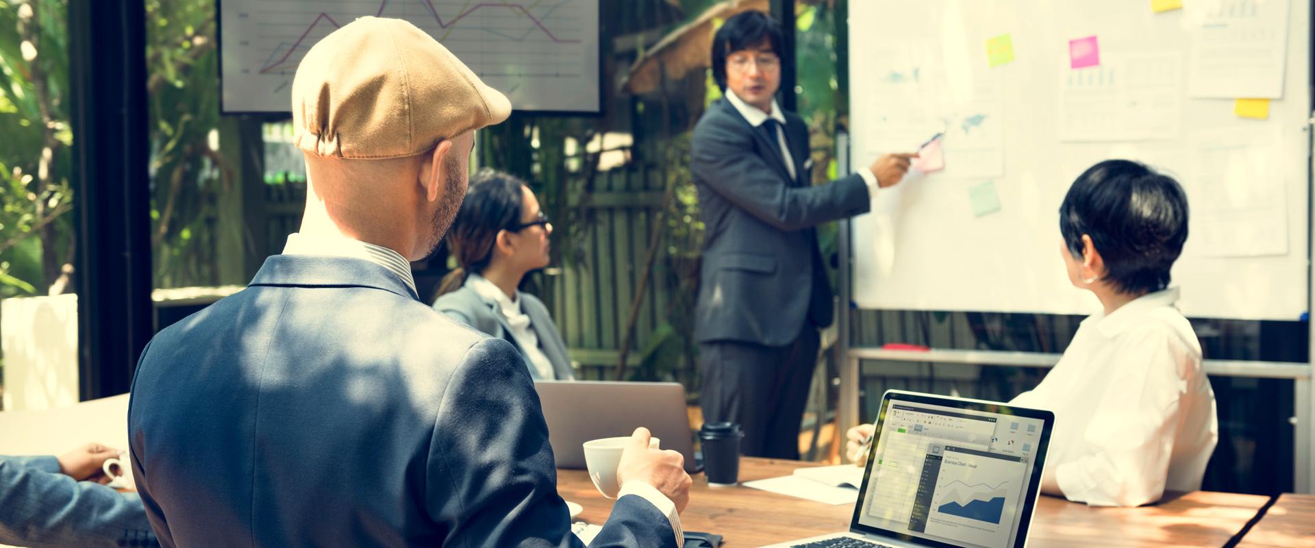 groupe de personnes travaillant et plannifiant à l'aide d'un tableau